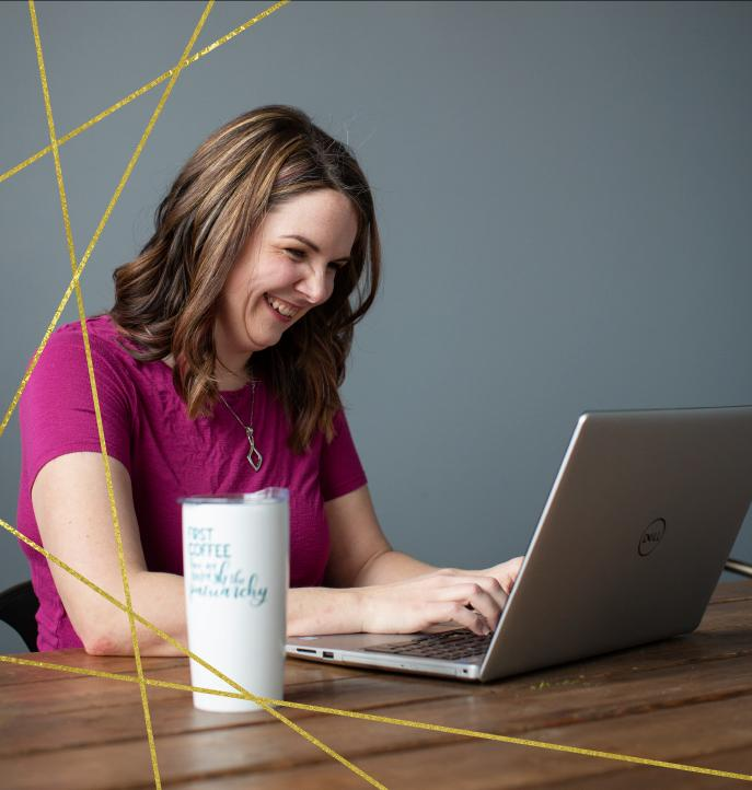 """Meg working on computer drinking coffee out of mug that says """"first coffee then we smash the patriarchy"""""""